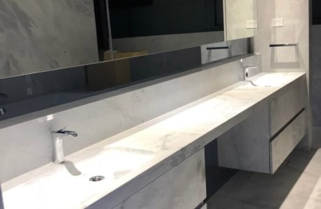 Custom-made-floating-ensuite-with-marble-fronts-and-Benchtops-aluminium-frame-shaving-cupboard-doors-with-metal-blades